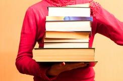 Ett stort antal böcker i händerna Arkivfoton