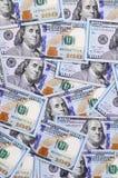 Ett stort antal US dollarräkningar av en ny design med ett blått band i mitt Top beskådar arkivfoton