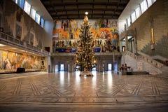 Ett stort inomhus julträd med en stjärna överst arkivfoton