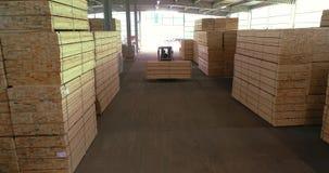 Ett stort lager av timmermaterial En gaffeltruck b?r en tr?str?le till och med lagret Trevligt staplad tr?st?ng stock video