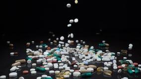 Ett stort och omväxlande sortiment av läkemedlet förgiftar, eller vitamintillägg faller mot en svart bakgrund stock video