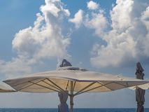Ett stort paraply från solen mot den blåa himlen, de fluffiga molnen och havet solig dag Royaltyfri Bild