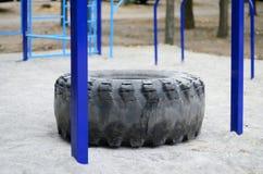 Ett stort svart gummihjul mot ett gatasportfält för utbildande friidrottfriidrott och crossfit Utomhus- idrotts- idrottshallequip Arkivfoto