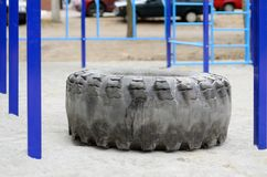 Ett stort svart gummihjul mot ett gatasportfält för utbildande friidrottfriidrott och crossfit Utomhus- idrotts- idrottshallequip Arkivbild