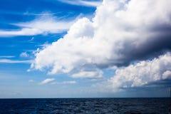 Ett stort tungt moln ovanför det blåa havet royaltyfri bild