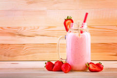 Ett stort, tunt och rakt rött sugrör i kruset med drycken Några jordgubbar är nära en full krus av jordgubbedrinken Arkivfoto
