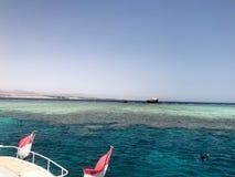 Ett stort vitt skepp, ett fartyg, en turist- eyeliner för kryssning med två egyptiska flaggor på ett blått azurt hav, ett hav med Arkivfoto