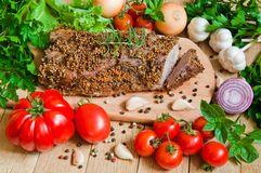 Ett stycke av bakat nötkött med nya grönsaker på en trätabell Royaltyfri Bild