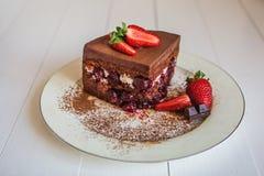 Ett stycke av chokladkaka och körsbär och vitkräm dekoreras med jordgubbar arkivfoton