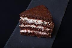 Ett stycke av chokladkakan kritiserar på plattan på svart bakgrund Arkivbild