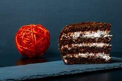 Ett stycke av chokladkakan kritiserar på plattan på svart bakgrund Se Royaltyfria Bilder