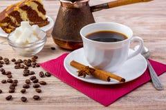 Ett stycke av chokladkakan med den vita koppen av svart varmt kaffe på tefatet som tjänas som med kaffebönor, kuber för vitt sock Fotografering för Bildbyråer