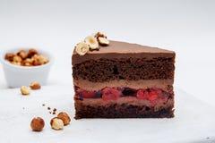 Ett stycke av chokladkakan med körsbär och hasselnöten på vit bakgrund Läckra chokladkakor på tabellnärbild arkivfoto
