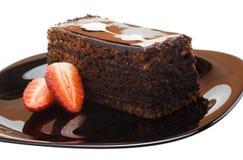 Ett stycke av chokladkakan på en platta med jordgubbar Arkivbilder