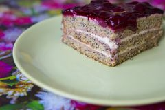 Ett stycke av den körsbärsröda kakan för vallmo på en platta Fotografering för Bildbyråer