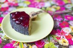 Ett stycke av den körsbärsröda kakan för vallmo på en platta royaltyfria foton