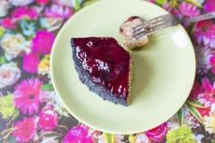 Ett stycke av den körsbärsröda kakan för vallmo på en platta Royaltyfri Fotografi