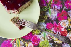 Ett stycke av den körsbärsröda kakan för vallmo på en platta arkivbilder