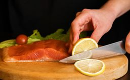 Ett stycke av den röda fisken på ett träbräde, kniv ligger på tabellen nära fisken royaltyfria foton