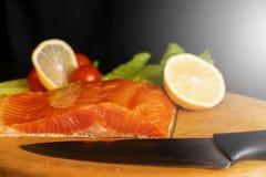 Ett stycke av den röda fisken på ett träbräde, kniv ligger på tabellen nära fisken royaltyfri bild