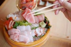 Ett stycke av den skivade japanska fisken är tången vid selektiva pinnar arkivfoton