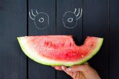 Ett stycke av en biten och saftig vattenmelon på en bakgrund av en träyttersida av svart färg royaltyfria bilder