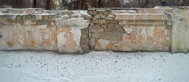 Ett stycke av en förstörd tegelstenvägg som täckas med snö stock illustrationer