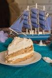 Ett stycke av en luftig Kiev kaka på en vit platta med ett skepp på ett b royaltyfria foton