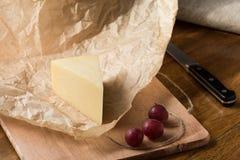 Ett stycke av hårdost som slås in i papper och röda druvor på köksbordet arkivfoton
