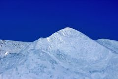 Ett stycke av is i form av berg på en blå bakgrundsmakro royaltyfria bilder