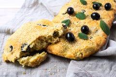 Ett stycke av italienskt bröd Focaccia med oliv och örter royaltyfri fotografi