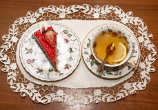 Ett stycke av jordgubbepajen och en kopp te Arkivbild