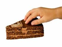 Ett stycke av kakan och en hand royaltyfri bild