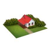 Ett stycke av land med gräsmatta med huset och buskar Arkivbild
