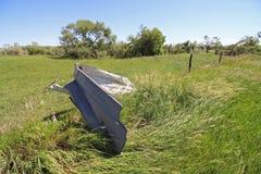 Ett stycke av metallskräp som slås in runt om en staketstolpe av en tromb Arkivfoto