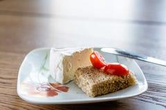 Ett stycke av mjuk ost och tomater Royaltyfri Bild