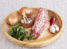 Ett stycke av nytt marmorerat nötkött, chilipeppar, persilja, löken, vitlök, stöd ligger på ett trämagasin Royaltyfri Fotografi