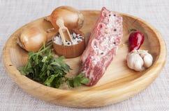 Ett stycke av nytt marmorerat nötkött, chilipeppar, persilja, löken, vitlök, stöd ligger på ett trämagasin Arkivfoton