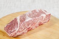 Ett stycke av nytt marmorerat nötkött, stöd ligger på ett trämagasin Arkivfoton