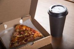 Ett stycke av pizza i en individuell kartong och en plast- kopp för kaffe Fotografering för Bildbyråer