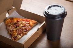 Ett stycke av pizza i en individuell kartong och en plast- kopp för kaffe Royaltyfri Foto