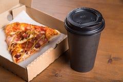 Ett stycke av pizza i en individuell kartong och en plast- kopp för kaffe Royaltyfria Foton