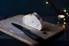 Ett stycke av vitt bröd på en skärbräda Royaltyfri Bild