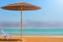 Ett sugrörparaply och en vit stolställning på en sandig strand nära vattnet Vila på det döda havet i Israel som förbiser bergen fotografering för bildbyråer