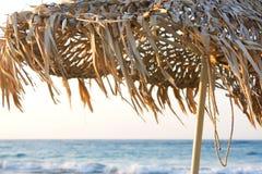 Ett sugrörsolparaply på stranden Arkivfoto