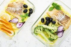 Ett sunt mål för ett mellanmål är en lunchask Glass behållare med den nya ångahavsfisken, ris med gurkmeja som är ny royaltyfri bild