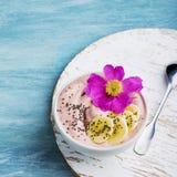 Ett sunt vegetariskt frukostmellanmål: smoothies från en djupfryst banan och en djupfryst jordgubbe med kokosnöten mjölkar i a Arkivfoton
