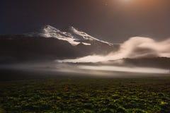Ett sväva moln i närheten av den sova Elbrus vulkan i Kaukasuset på natten i ljuset av månen Royaltyfri Fotografi