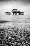 Ett svartvitt av den gamla utbrända pir i Brighton royaltyfri bild