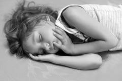 Ett svartvitt foto av lite flickan som sover i en säng Arkivfoto